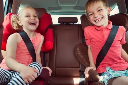 Two kids smiling in the back seat